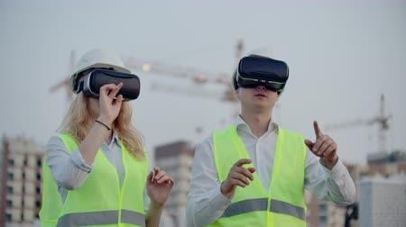 felügyelő : Two inspectors of the future on the construction site use virtual reality glasses on the background of buildings and cranes.