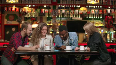 memories photos : Portrait of cheerful young friends looking at smart phone while sitting in cafe. Mixed race people sitting at a table in restaurant using mobile phone Stock Footage