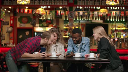 memories photos : A multiethnic group of students, three Europeans and an African American, look at the phone screens, laugh and discuss. Talk with friends and watch photos on the phone Stock Footage