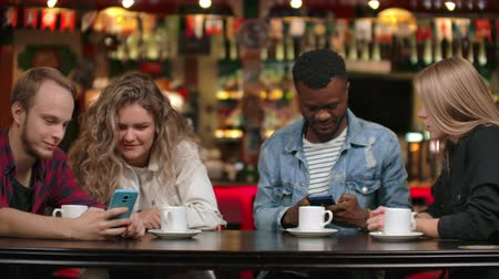 make friends : Group of friends at a bar drinking coffee and discussing while looking at the screen of a smartphone Stock Footage