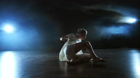 balerína : Modern dance woman in a white dress dances a modern ballet, jumps, makes rotation on the stage with smoke in the blue spotlights.