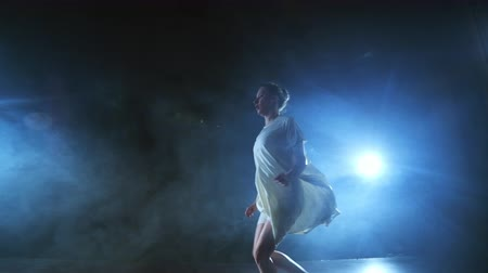 balerína : Zoom camera moves around the stage with software and smoke. Girl ballerina dancing in a white dress spinning plastic while performing pirouettes and rotations, experiencing emotions