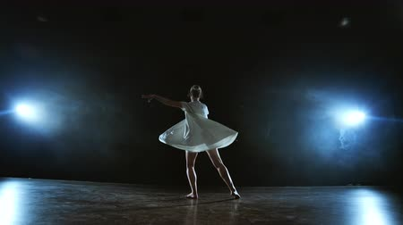 whirling : The zoom camera moves the woman dancer across the stage with software and smoke. A modern dramatic ballet, a woman in a white dress spins on one leg and jumps.