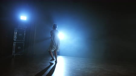 balerína : The zoom camera moves the woman dancer across the stage with software and smoke. A modern dramatic ballet, a woman in a white dress spins on one leg and jumps.