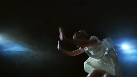 balerína : Modern girl dancer in a white short dress performs plastic beautiful dramatic dances, running across the stage, falling to the floor and spinning. Lanterns and smoke Dostupné videozáznamy