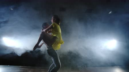 balerína : Zoom camera, a female dancer jumps onto her partner shoulder. Acrobatic dance musical on stage in smoke. Contemporary Contemp