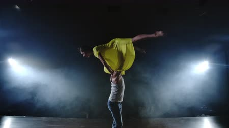 balerína : Zoom camera, two modern ballet dancers are dancing on stage in smoke a man raises his partner in his arms and rotates in the air. The musical uses circus acrobats dancers Dostupné videozáznamy