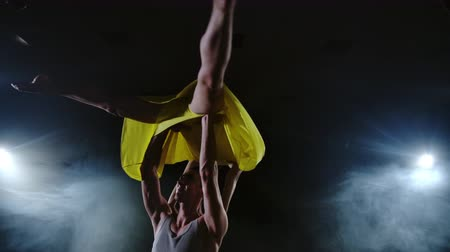 balerína : Two dancers a man and a woman run to each other and a male partner raises a woman in a yellow dress in her arms and rotates in the air performing top support Dostupné videozáznamy