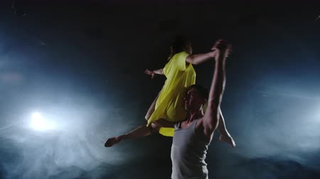 elevação : Two dancers a man and a woman run to each other and a male partner raises a woman in a yellow dress in her arms and rotates in the air performing top support Stock Footage