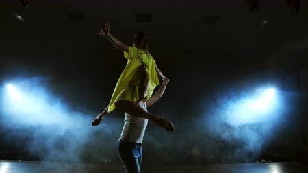 позы : Two dancers a man and a woman run to each other and a male partner raises a woman in a yellow dress in her arms and rotates in the air performing top support Стоковые видеозаписи