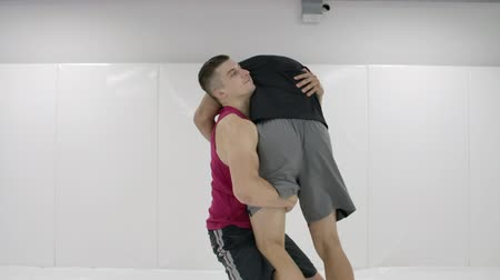 колготки : Greco-Roman wrestlers in a white room with mats. Practicing self-defense techniques. Throw and pain Стоковые видеозаписи
