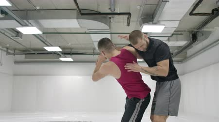zapasy : Greco-Roman wrestlers in a white room with mats. Practicing self-defense techniques. Throw and pain Wideo