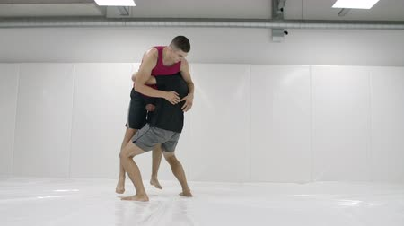 klatka : The camera moves after the men wrestlers. MMA fighters work out wrestling equipment on training tracks. Capturing, throws and painful moves