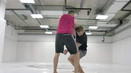 worstelaar : The camera moves after the men wrestlers. MMA fighters work out wrestling equipment on training tracks. Capturing, throws and painful moves