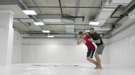 konkurenti : Two male wrestlers in a white room work out throwing mats. Take a grapple and throw through yourself