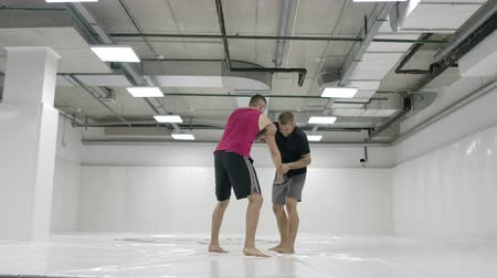 grapple : Two male wrestlers in a white room work out throwing mats. Take a grapple and throw through yourself