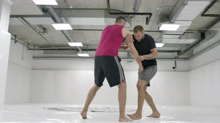 opponent : Greco-Roman wrestlers in a white room with mats. Practicing self-defense techniques. Throw and pain Stock Footage