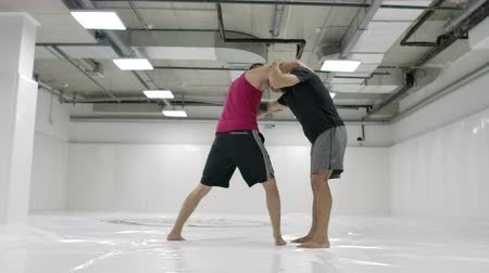 grappling : Two wrestlers perform in slow motion. Greco-Roman wrestlers train in the hall in T-shirts and coats. Stock Footage