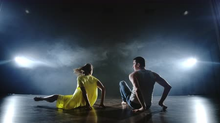 dominação : A man and a woman dance together a funny dance in jeans and a yellow dress on stage in smoke. Musical