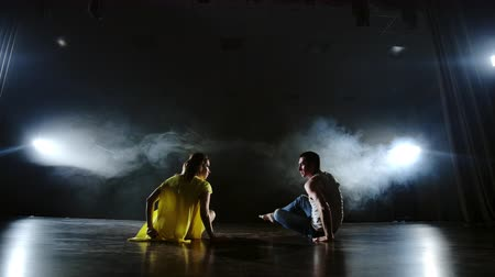balerína : Zoom camera. Modern romantic choreography. Love is on stage. A man and a woman dance together a funny dance in jeans and a yellow dress on stage in smoke. Musical