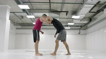 escola : The wrestler moves to the opponent, grabs and rolls with finishing on the mats in slow motion.