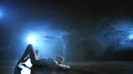 balerína : A woman in a white dress is dancing on the stage the dramatic dances of modern ballet. A ballet dancer moves plastic performing modern choreography in smoke