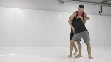 grappling : Greco-Roman wrestlers in a white room with mats. Practicing self-defense techniques. Throw and pain Stock Footage