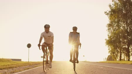 íngreme : A man and a woman ride sports bikes on the highway at sunset in gear and protective helmets in slow motion 120 fps Stock Footage