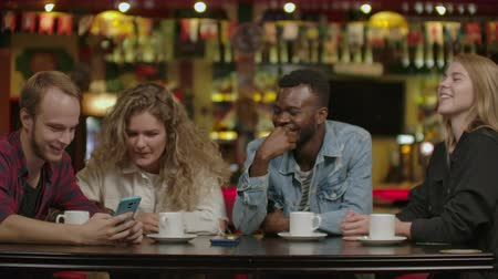 kahve molası : Happy multi-ethnic group of friends talking using smartphones at. Happy multi ethnic group of friends talking using smartphones in cafe, diverse young people. Stok Video
