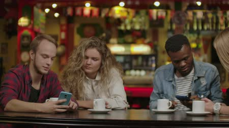 mates : Beautiful Hispanic man Shows Interesting Stuff on Her Smartphone to Her Friends while They Have Good Time in Bar. They Laugh, Joke, Drink in Stylish Hipster Bar Establishment