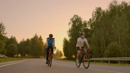 Empty Space. Sporty friends on bicycle on sunset. Couple cyclist go along coast. Sport in Nature background. Group of people two road biker in sunset Stok Video