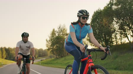 fixní : Cyclist Riding On Road Bike Rear View.Cycling Men Pedalling Road Bicycle On City Park.Tracking Shot Of Cyclist Rides On Road Bike At Sunset Sun.Cyclist Athlete Intensive Training On Bicycle.