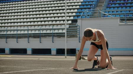 závodní dráha : Slow motion: Girl athlete waits for start of race in 400 meters. girl athlete waits for start of race in 100 meters during. Running at the stadium from the pads on the treadmill.