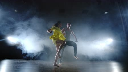 гибкий : a couple of dancers on stage in smoke and spotlights moving fast