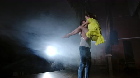 balerína : a couple is dancing doing acrobatic tricks on stage in smoke and spotlight