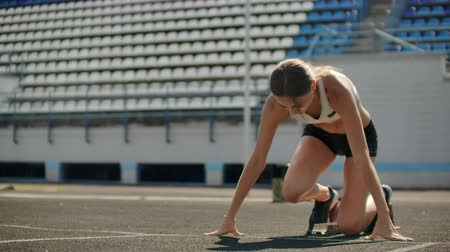 stopa : Slender young girl athlete is in position to start running in the pads on the track in slow motion. Dostupné videozáznamy