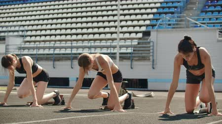 トラック : Female runners at athletics track crouching at the starting blocks before a race. In slow motion