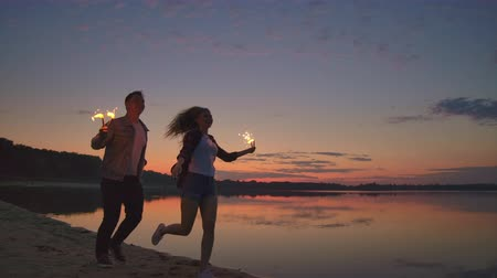 bengália : Young happy multiethnic couple holding burning sparkling candles and running by the sea during sunset. Slow motion shot. Stock mozgókép