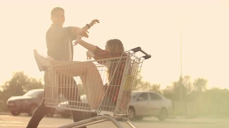 troli : Side view of a young female and male having fun outdoors on shopping trolleys. Multiethnic young people racing on shopping carts. On the parking zone with their