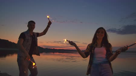 bengálsko : Young happy multiethnic couple holding burning sparkling candles and running by the sea during sunset. Slow motion shot. Dostupné videozáznamy