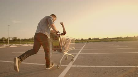 empurrando : Back view. Cheerful young couple in love man and woman laughing and having fun while riding carts in supermarket parking in slow motion at sunset Stock Footage