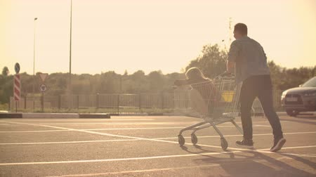 torcendo : Back view. Cheerful young couple in love man and woman laughing and having fun while riding carts in supermarket parking in slow motion at sunset Vídeos