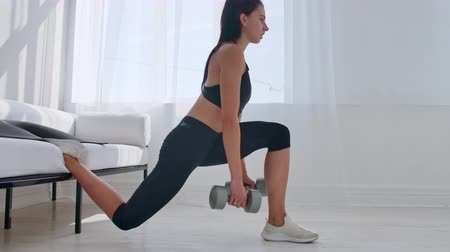squatting : Brunette in black sportswear in a white apartment makes a split squat with dumbbells in her hands leaning on the sofa with her foot Stock Footage
