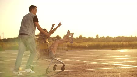 troli : Back view. Cheerful young couple in love man and woman laughing and having fun while riding carts in supermarket parking in slow motion at sunset Stock mozgókép