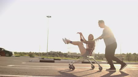 troli : Young friends having fun on shopping trolleys. Multiethnic young people racing on shopping cart. slow motion.