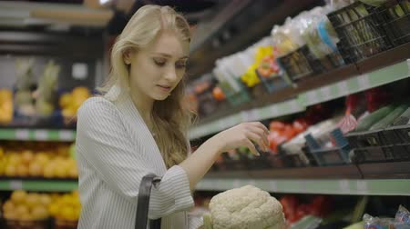 beslissen : Young beautiful brunette girl in her 20s picking out napa cabbage and cauliflower and putting them into shopping cart at the fruit and vegetable aisle in a grocery store. Stockvideo