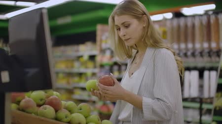 kalebas : Attractive young woman choosing apple at fruit vegetable supermarket marketplace. Stockvideo