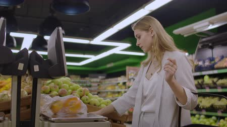 bakkal : A blonde girl in a supermarket weighs oranges on an electronic scale pressing the display standing with a basket in her hands. Stok Video