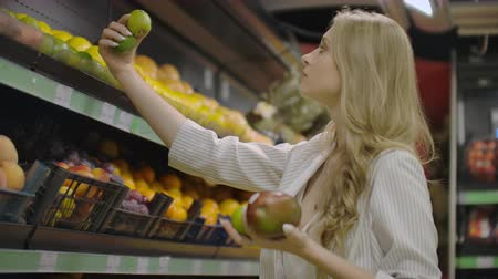 beslissen : Young Woman Choosing Ripe Mangoes in Grocery Store. Vegan Zero Waste Girl Buying Fruits and Veggies in Organic Supermarket and Using Reusable Produce Bag. 4K Slow motion. Stockvideo