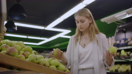 kalebas : Woman selecting fresh red apples in grocery store supermarket sale, shopping marketplace food taking choosing apples girl with bag buying apples at shopping basket